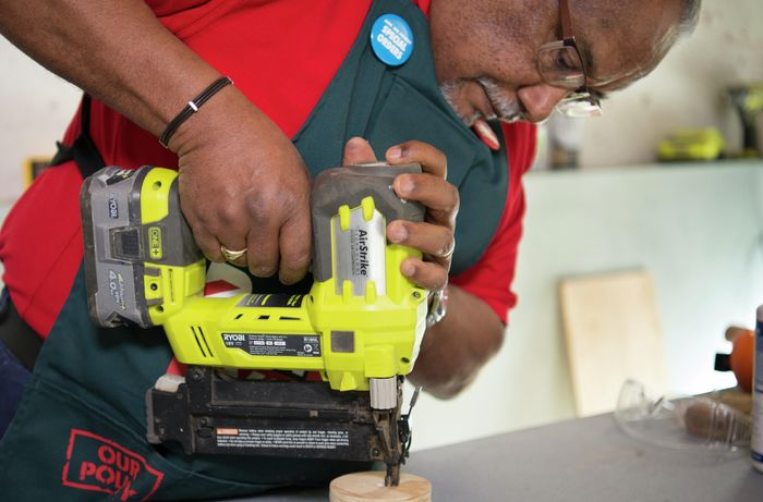 A person attaching a plywood circle to a piece of dowel using a cordless driver