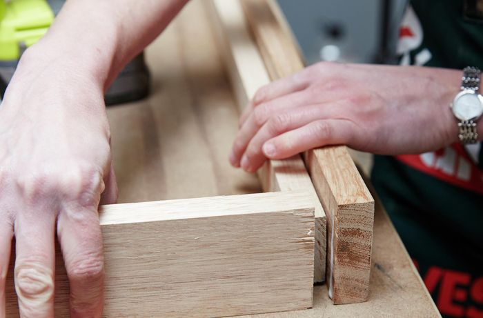 Person connecting timber frame together using glue