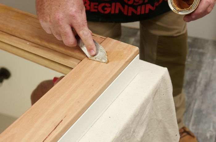 A person filling a gap in a piece of timber using wood filler