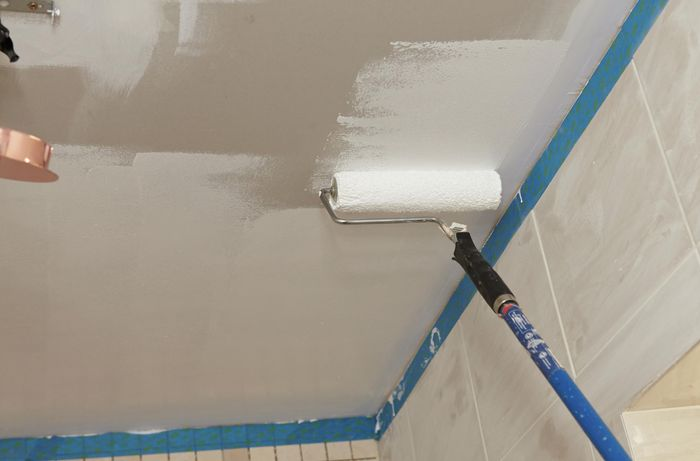 A ceiling being painted with an extension roller, with masking tape around the wall edges