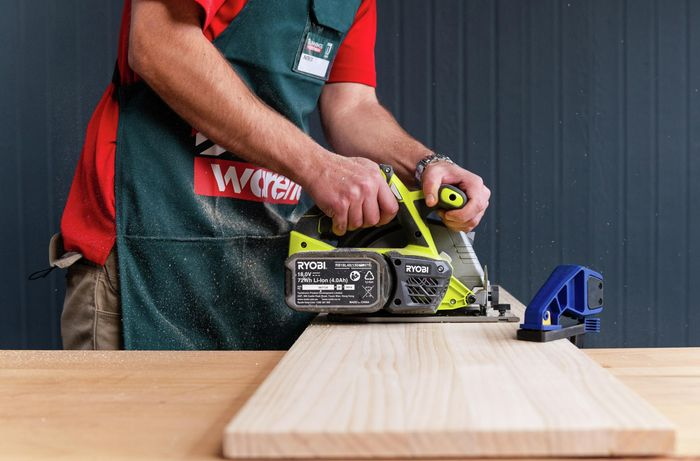 Bunnings team member cutting timber with a power saw