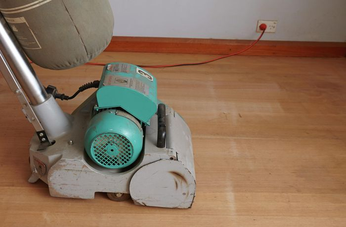 A floor sander on a hardwood floor