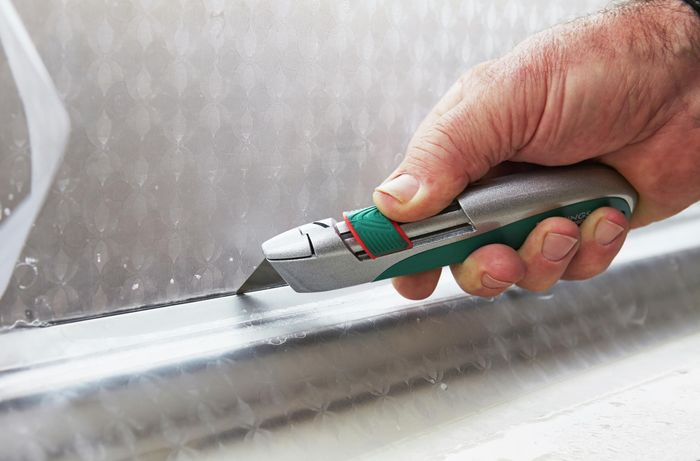 A person trimming frosting along the edge of a window using a trimming knife