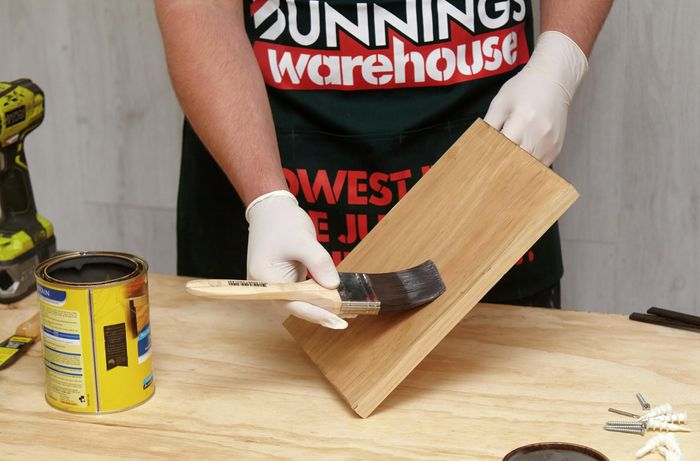 A person coating a small timber shelf with clear varnish