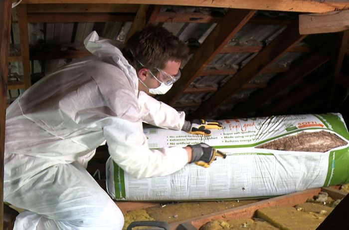 A person wearing protective gear opening a bag of insulation inside a roof space