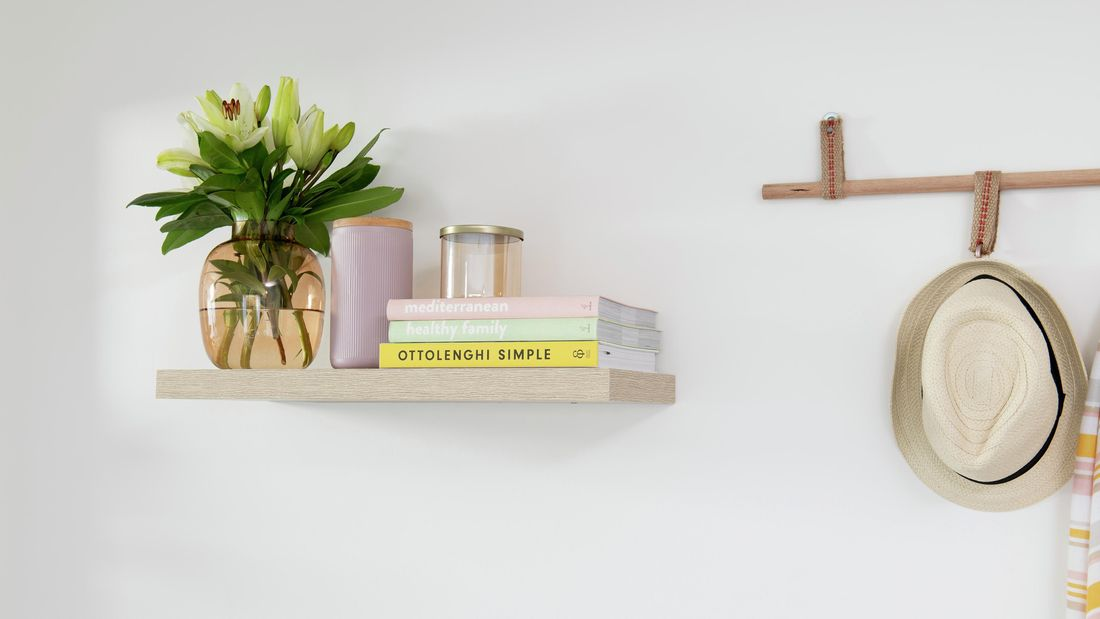 A completed and mounted floating shelf, holding vases and books