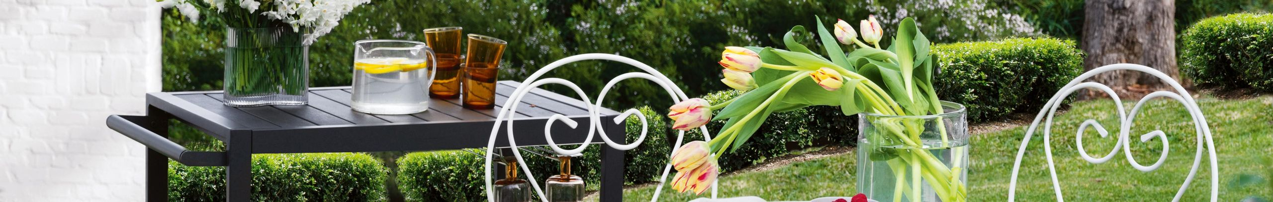 black bar table and white metal outdoor setting on lawn with fresh flowers and fruit