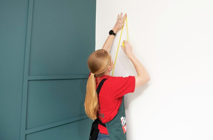 Person taping lines on wall.