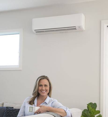 Woman sitting on couch holding air conditioner remote with air conditioning unit on wall behind her