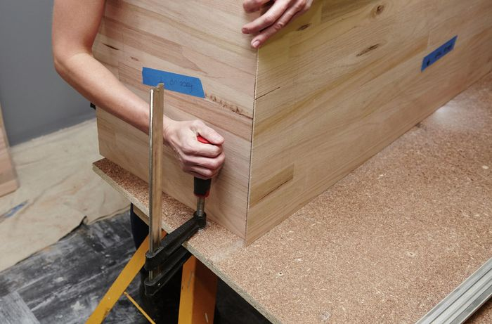 A person placing a clamp next to an L-shaped timber panel