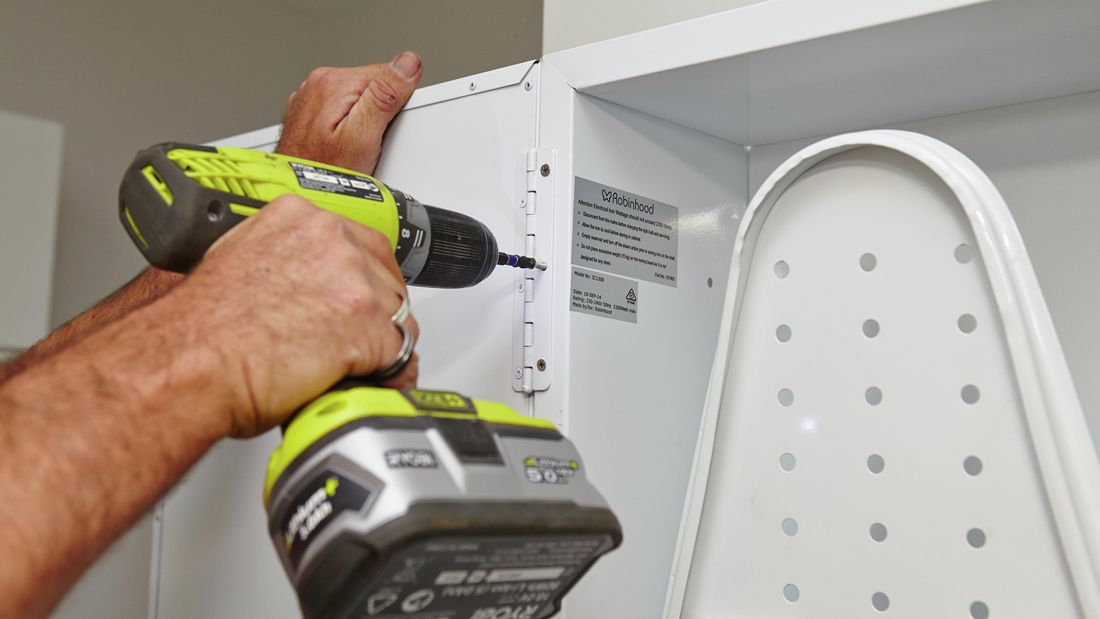 A Bunnings team member using the drill and screws to attach the door to the ironing centre.