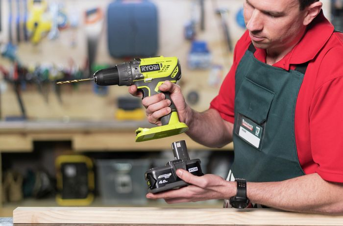 Team member showing the battery pack of a power drill