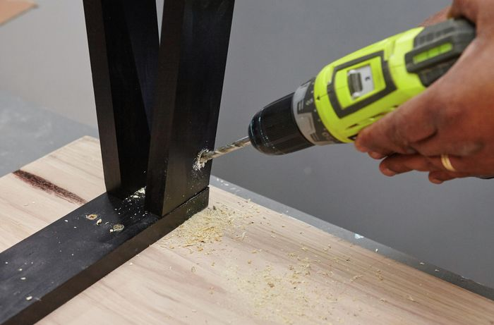 A person drilling into table legs on an inverted table