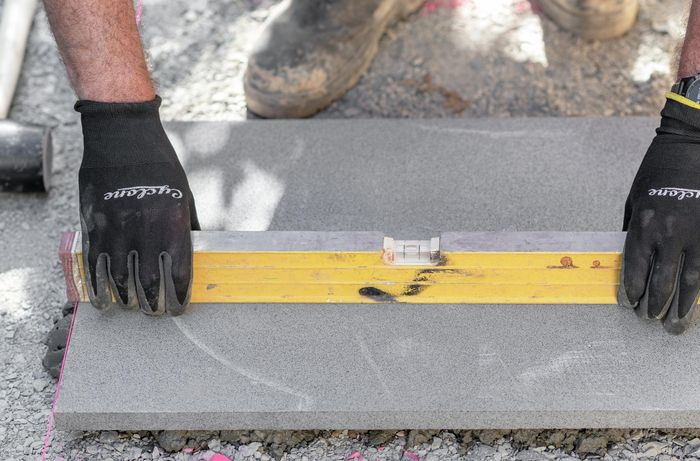 Person wearing protective gloves placing a spirit level across a paving stone.