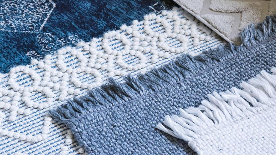 Close up of a white and blue textured rug.