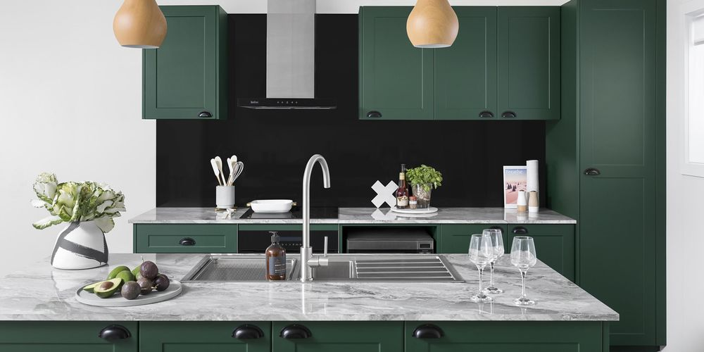 Forrest green cabinets in a traditional style kitchen with white marble countertop and matt black hardware