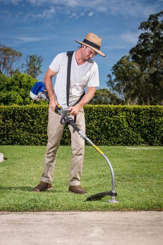 Man using grass trimmer to trim grass near path