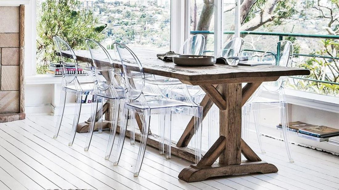 A rustic outdoor dining table paired with clear plastic chairs on an outdoor deck
