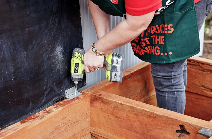 A lid hinge being screwed onto a sleeper compost bin with a power drill by a Bunnings team member