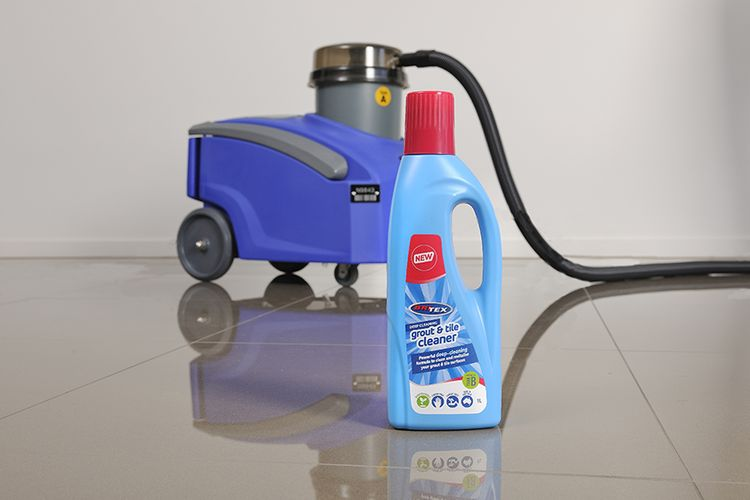 Bottle of tile and grout cleaner in front of vacuum cleaner