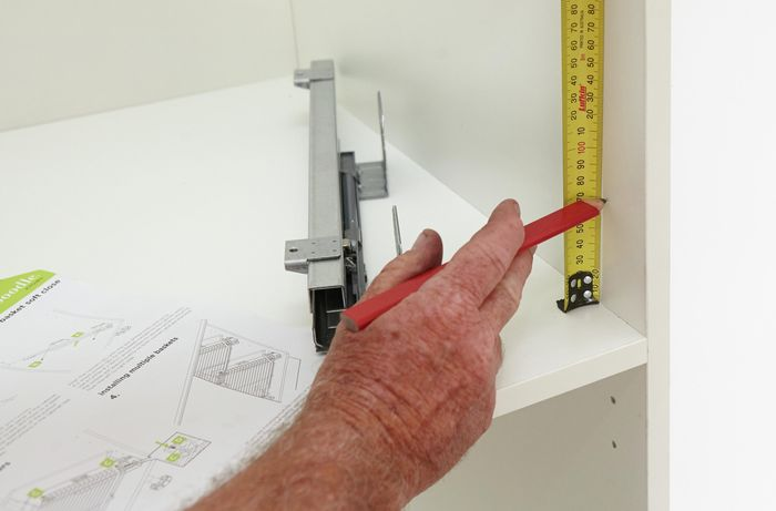 Person measuring inside of cupboard with measuring tape.