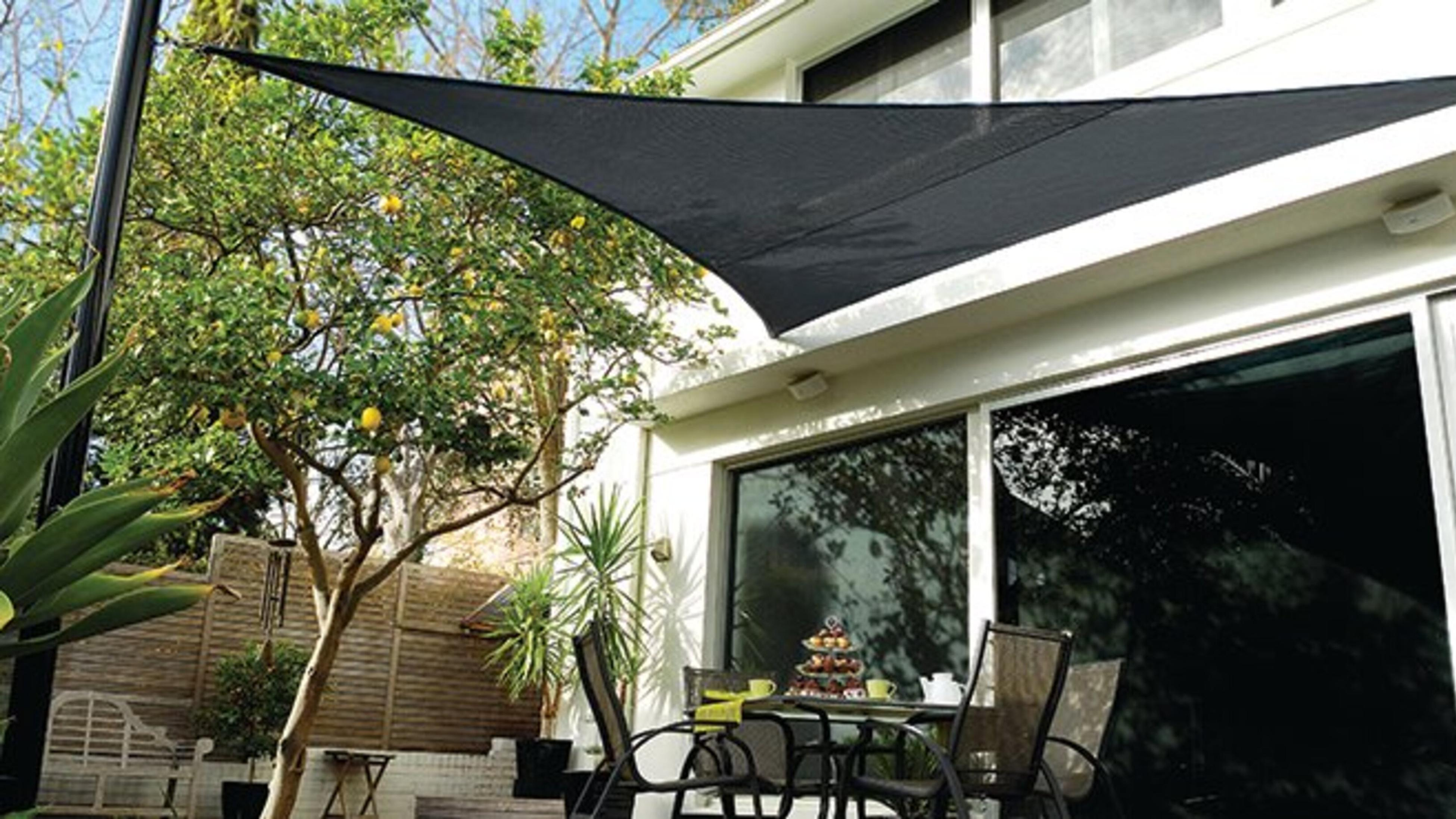 Black shade sail in outdoor area with trees.