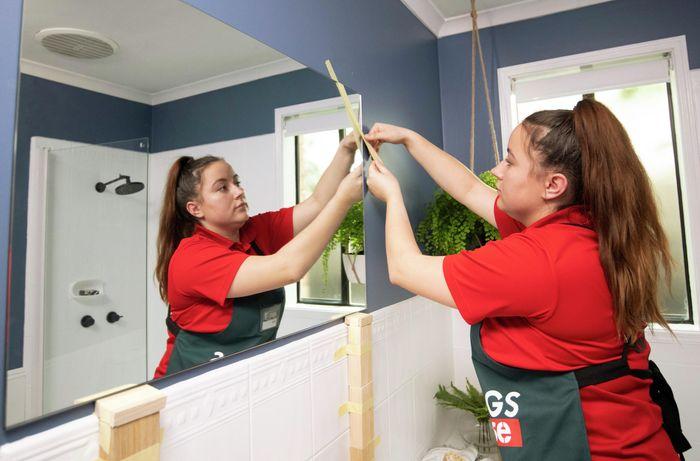 A person pressing a mirror against a wall