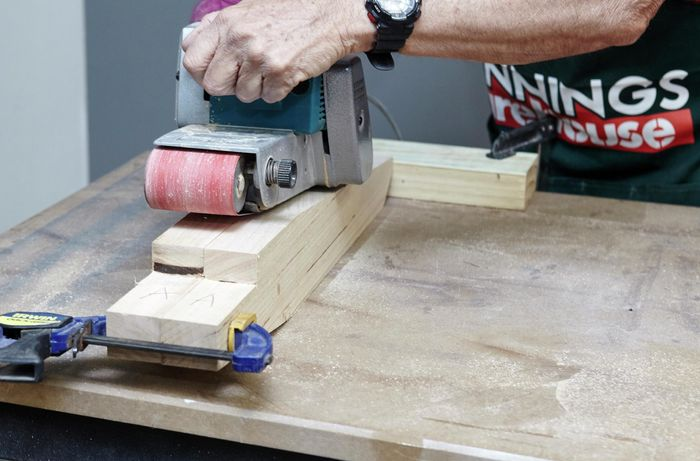 The two back supports of a wooden chair being sanded down with a belt sander, held together with a clamp