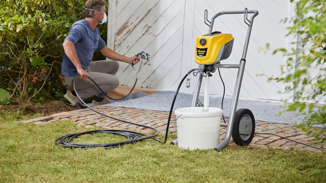 man using a spray gun to paint a shed in white