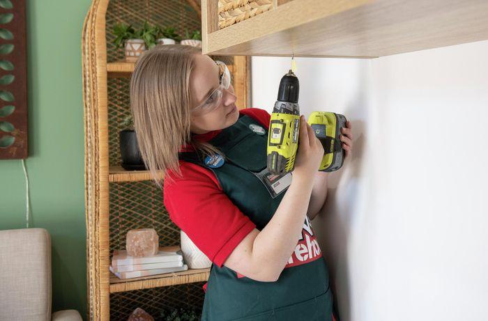 Person drilling hole into shelf