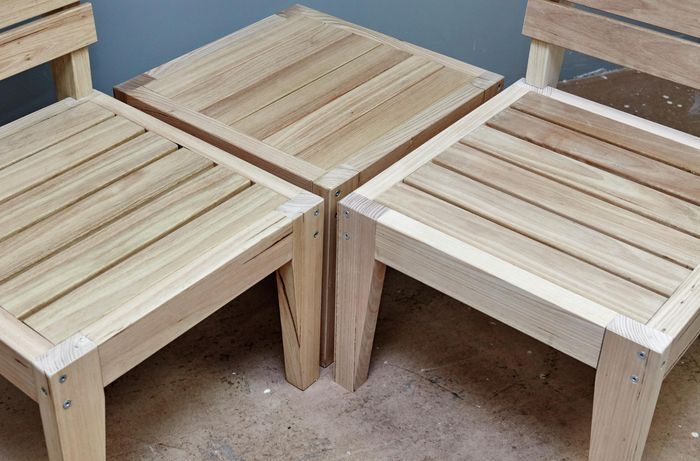A completed modular wooden outdoor furniture set, composed of two chairs and a coffee table