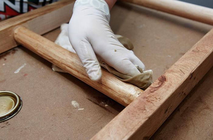 Person wiping DIY timber vintage ladder with rag and varnish.