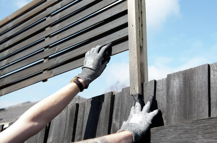 Gloved person attaching a fence extension to a wooden fence
