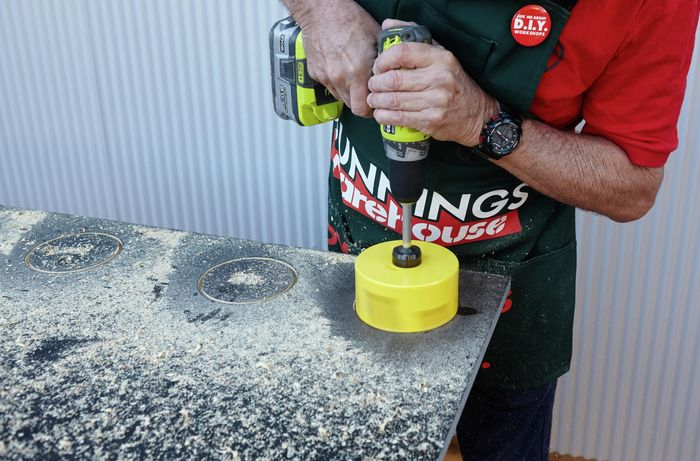 A hole saw being used to cut holes in the vertical garden tier for pot plants to sit in