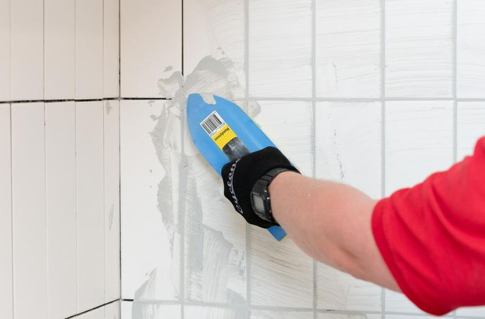 applying grout to the tiled area
