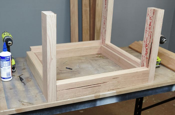 An unassembled wooden table, with a leg yet to be laid out, on a workbench