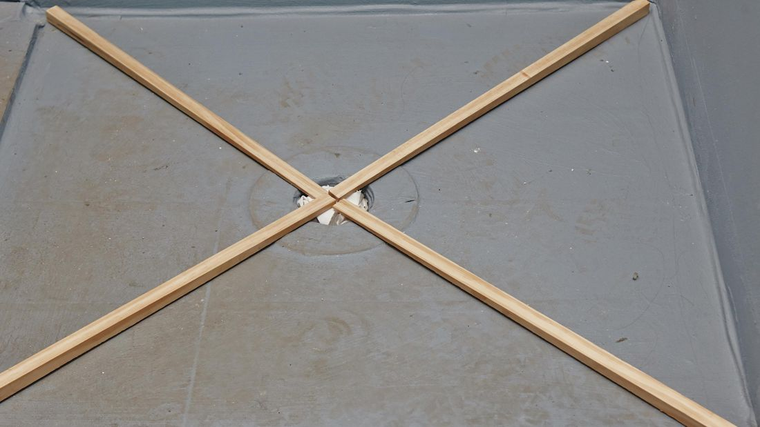 Four wedge-shaped lengths of timber laid in an X across a shower base