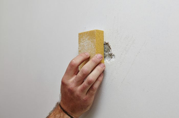 A person hand sanding a hole in a plaster wall