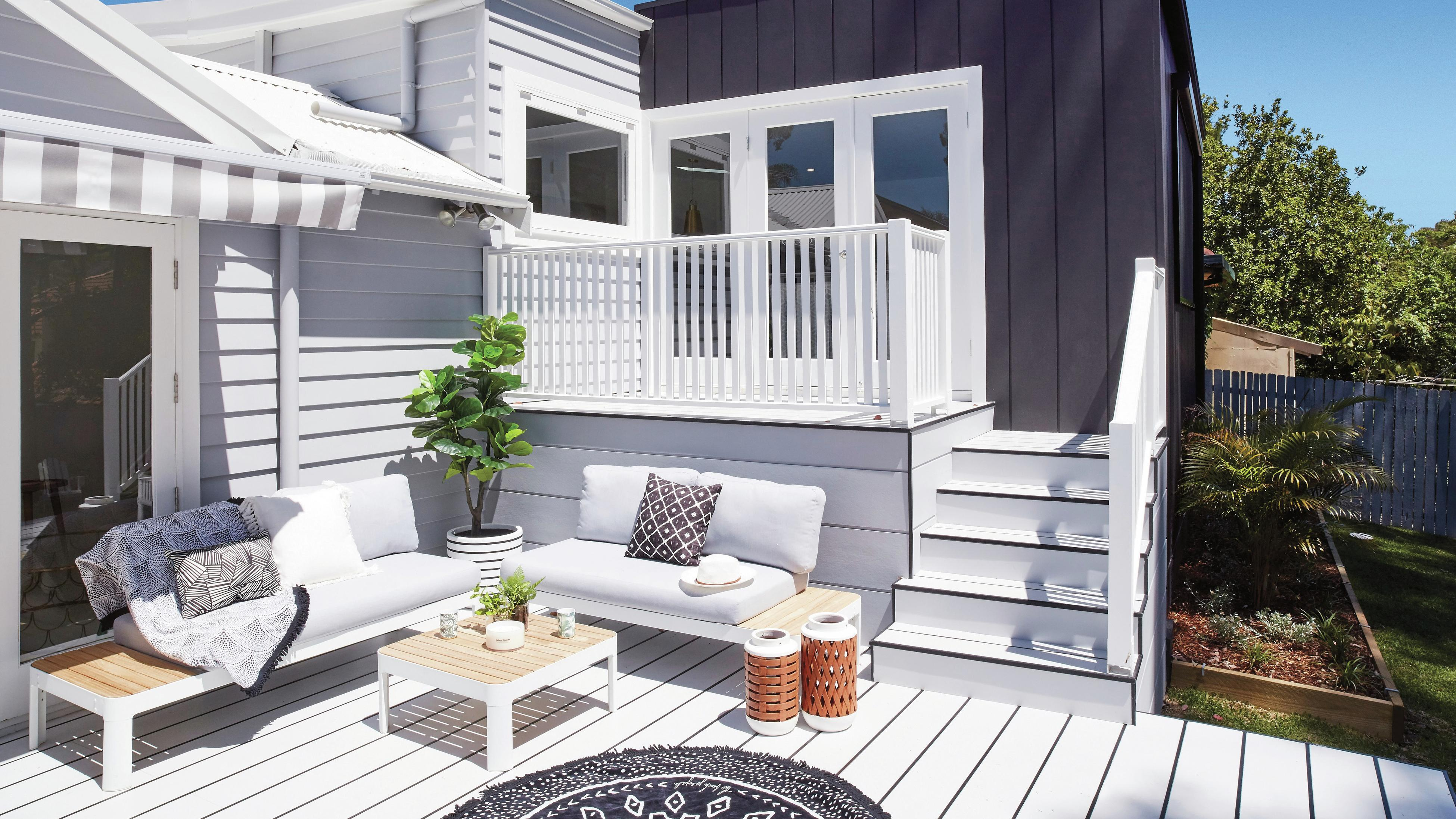 Outdoor area with white non-timber decking and coastal looking furniture.