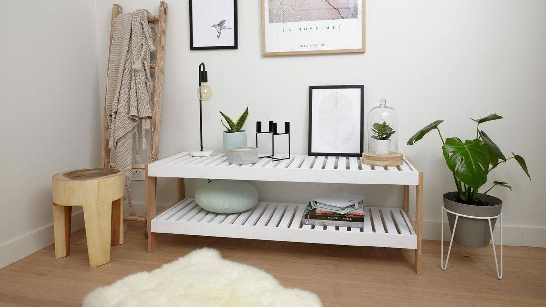 A slatted shelving unit in a brightly lit wooden themed room with a fur rug on the floor