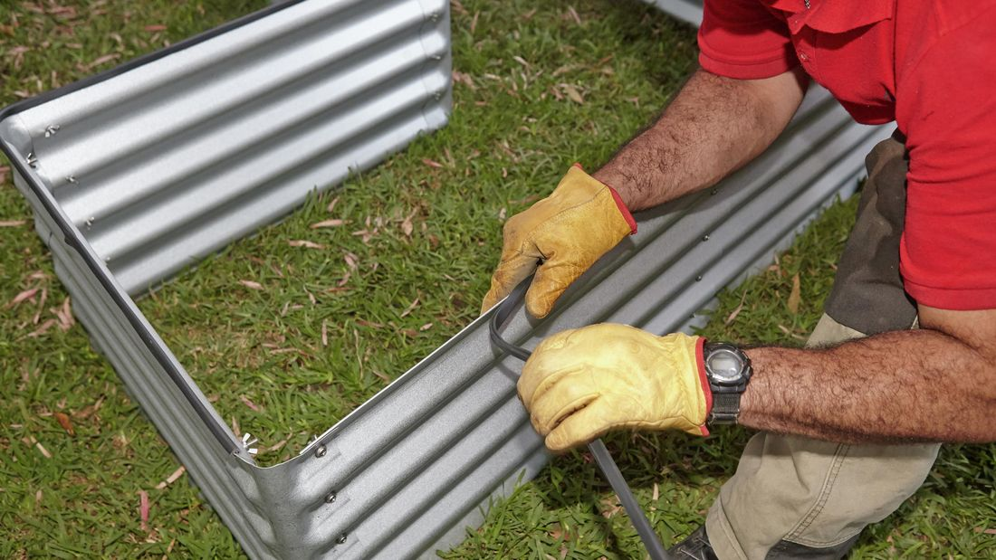 Person sticking protective edging to corrugated iron garden bed.
