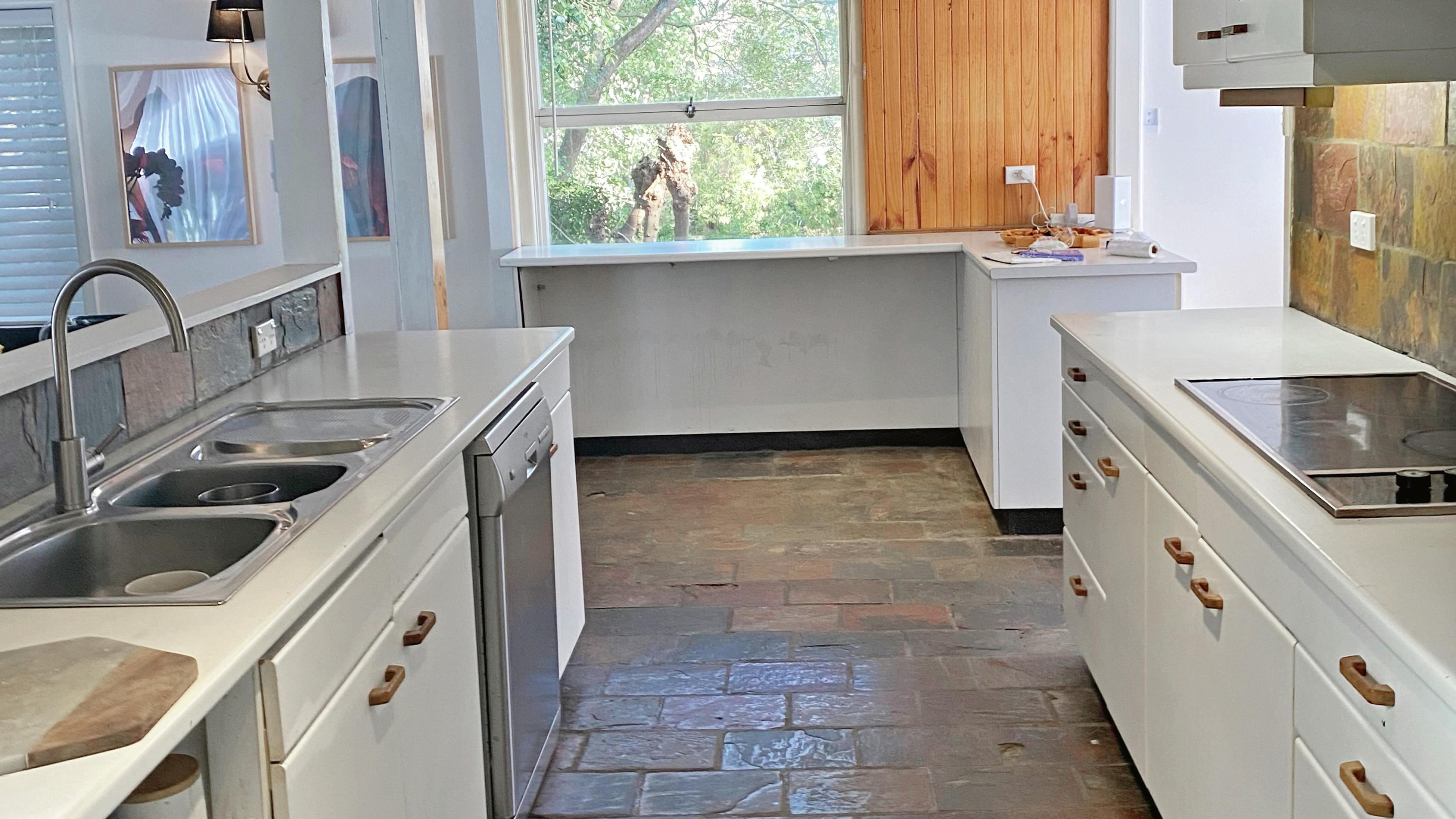 70's style warm toned kitchen with outdated cabinetry and the same large block tiles on the floor and the splashback