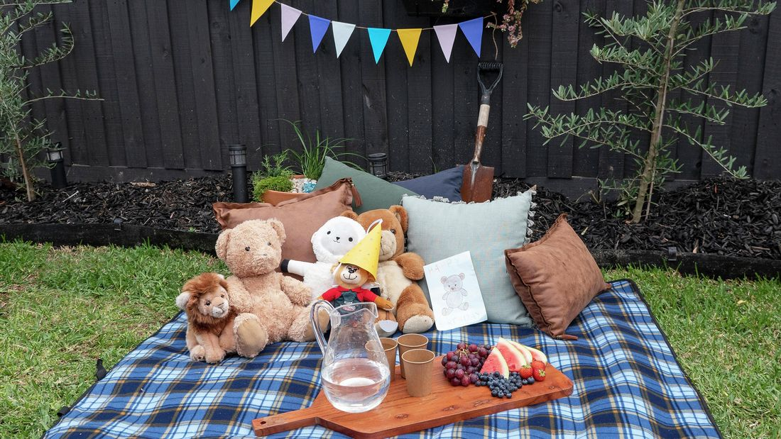 Picnic setting with cushions, soft toys and a cut board with drinks and fruit on it
