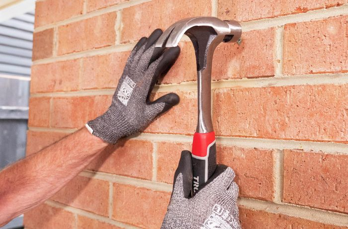 Person hammering wall plugs into brick.