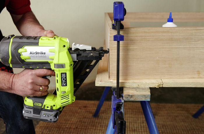 The base frame of a dog bed being assembled with a nailgun
