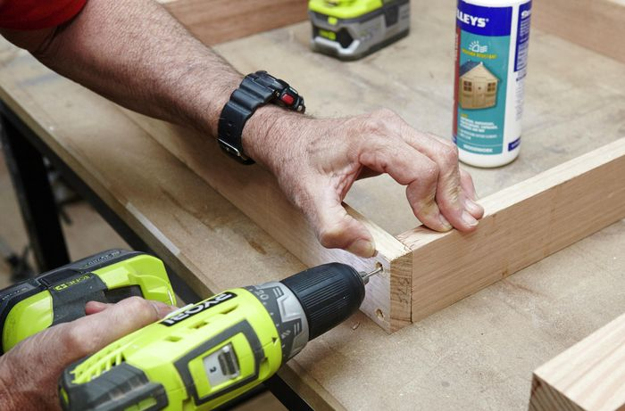 The subframe of an outdoor wooden table being screwed into place with a power drill