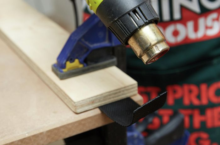 A heat gun being used to seal the end of a length of webbing