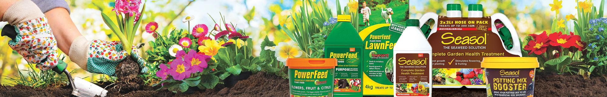 Person gardening with assorted packages of PowerFeed and Seasol fertilisers lined up.