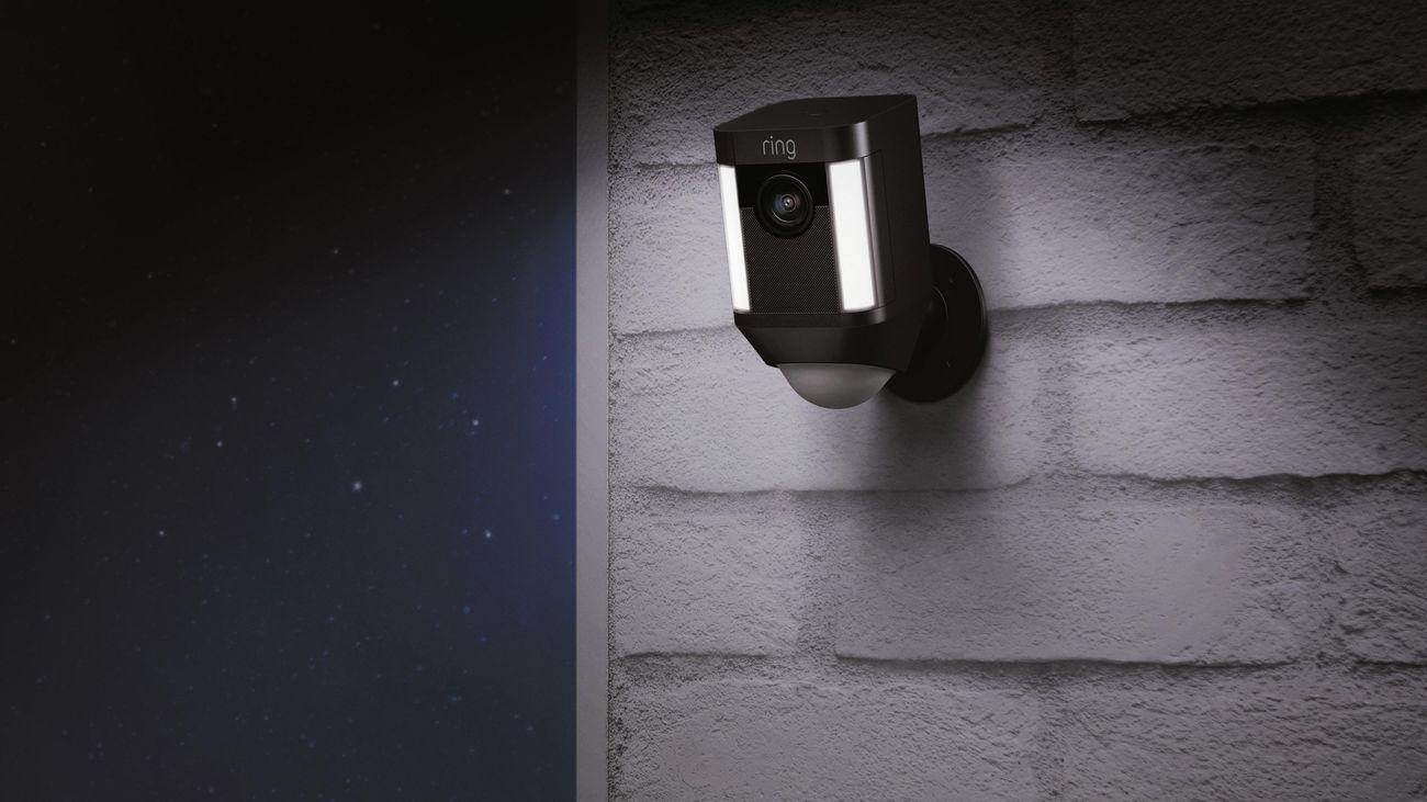 An outdoor spotlight camera hung on a brick wall