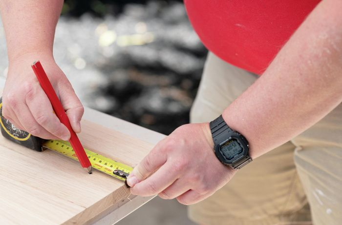 A Bunnings team member marking a piece of timber with measuring tape and a pencil